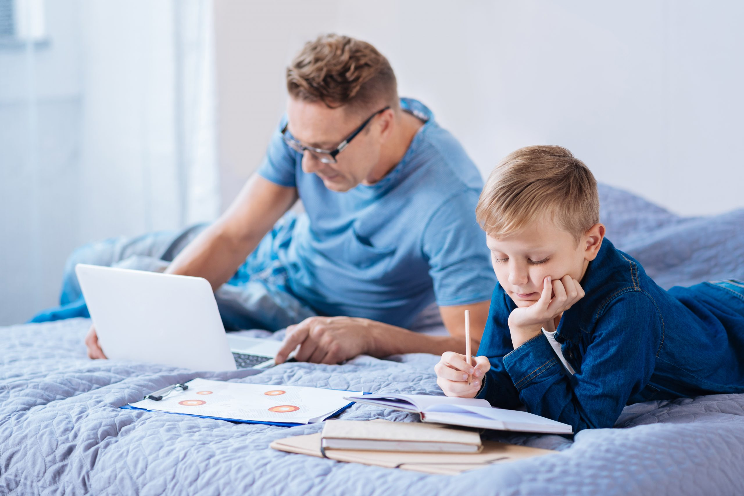Image of a father being a good role model to his studying son